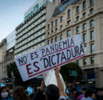 "Buenos Aires, Argentina - 9 july 2020: Anti lockdown protesters march in defiance of the government.  The poster says ""it is not a pandemic it is a dictatorship"""