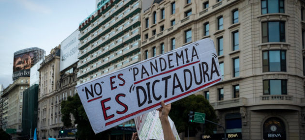 """Buenos Aires, Argentina - 9 july 2020: Anti lockdown protesters march in defiance of the government.  The poster says """"it is not a pandemic it is a dictatorship"""""""